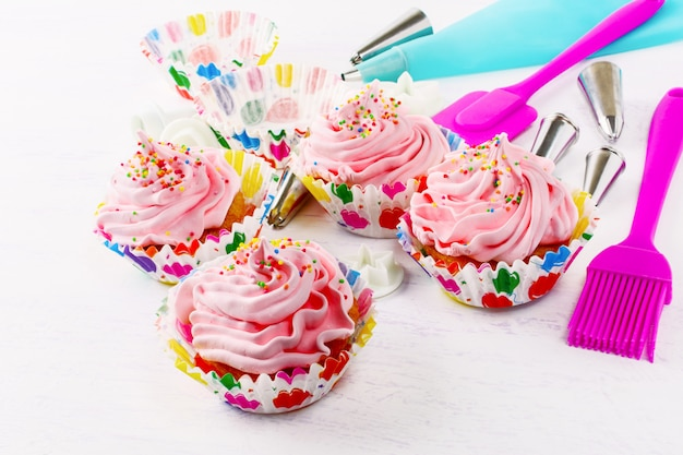 Cupcakes with pink whipped cream swirl and confectionery syringe