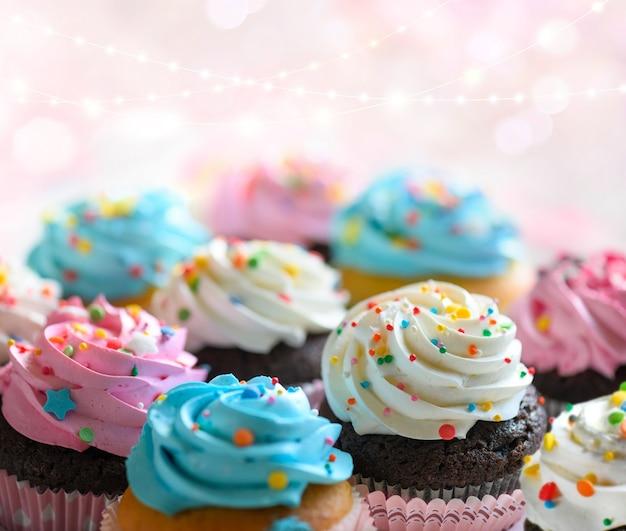 Кексы с розовыми белыми и голубыми сливками и красочными брызгами на розовом фоне с огнями боке. селективный фокус, неглубокая глубина резкости.