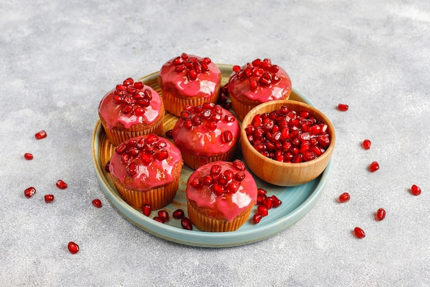 Cupcakes with pomegranate topping and seeds.