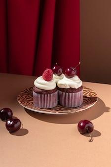 プレートにラズベリーとチェリーのカップケーキ