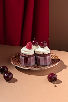 Cupcakes with raspberry and cherry on plate