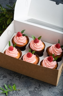 Cupcakes with raspberry cream, decorated with raspberries on top on gift wrap.