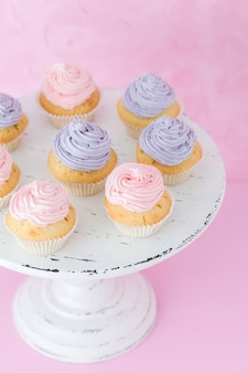 Cupcakes with violet and pink cream on white shabby shic stand on pastel pink background.