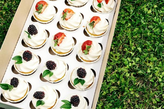 ボックスにホイップクリームとイチゴとブラックベリーのカップケーキ。