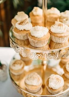 黄金のスタンドにホイップクリームとカップケーキ