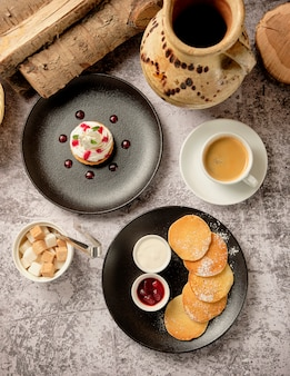 パンケーキとベリージャム、朝食にブラックコーヒーアメリカーノのカップとホイップホワイトバニラクリームのカップケーキ