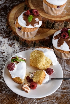 Cupcakes with white cream are watered with chocolate, rasped with raspberries and mint.