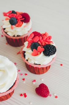 Cupcakes with white cream, fresh berries and decoration