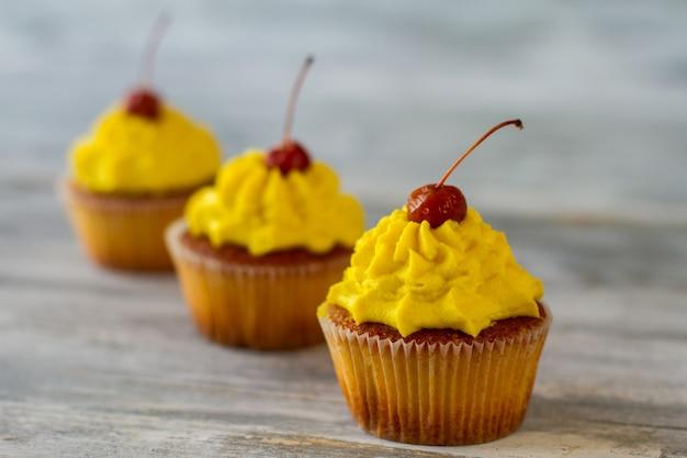 레몬 향이 나는 디저트 위에 노란색 설탕을 입힌 체리를 얹은 컵케이크는 인생을 더 달콤하게 만듭니다.