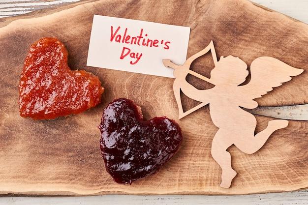 キューピッドとバレンタインデーの紙。カードの近くにジャムが入ったパン。ロマンスで朝を始めましょう。