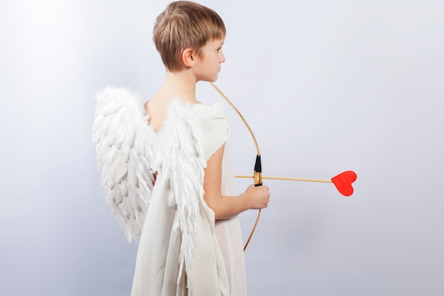 Cupid boy with wings and a shooting bow, at the end of the arrow a red heart.