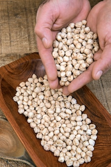 Cupped hands of man pouring raw chickpeas