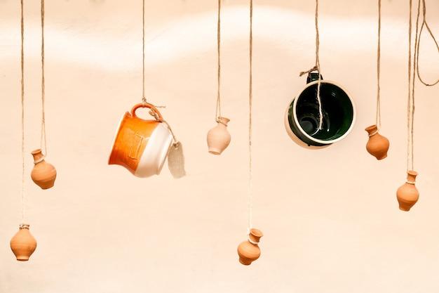 로프에 매달려 있는 컵과 항아리, 커피 바를 위한 레스토랑의 디자인과 인테리어, 판매 품목을 배치하는 창의적인 방법