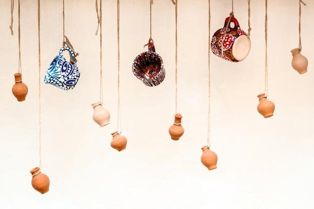 ロープにぶら下がっているカップと土鍋、コーヒーバーのレストランのデザインとインテリア、商品を販売するための創造的な方法 Premium写真