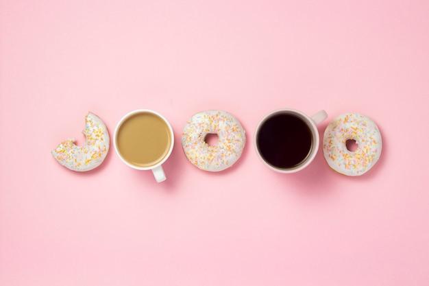 Чашки и бумажный стаканчик с кофе или чаем, свежие вкусные сладкие пончики выставлены в линии на розовом фоне. концепция быстрого питания, пекарня, завтрак, сладости, кафе. плоская планировка, вид сверху, копия пространства.