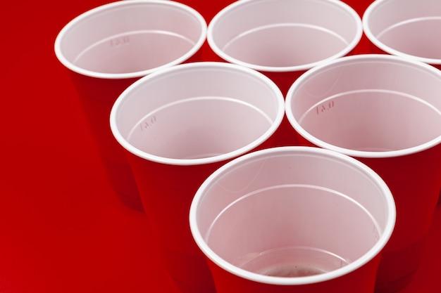 赤い背景の上のカップとプラスチックボール。ビアポンゲーム