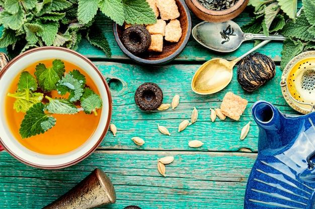 Чашки и чайник здорового травяного чая с мелиссой