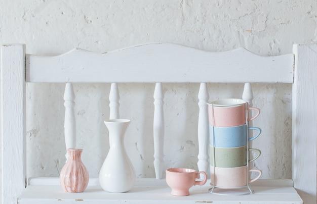 カップとヴィンテージの白い棚の上の花瓶