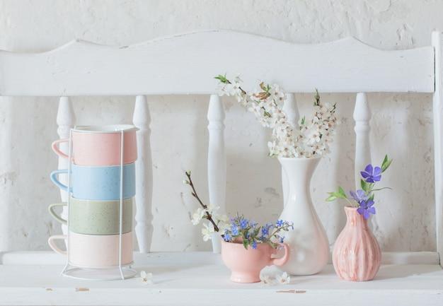 컵과 빈티지 나무 흰색 선반에 봄 꽃 화병