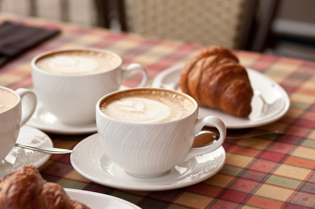 Cups of cappuccino coffee with croissant in a cafe