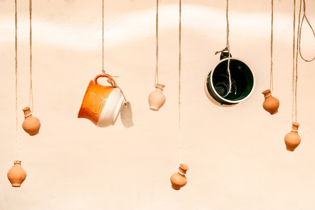 Cups and clay pots hanging on the ropes, the design and interior of the restaurant for a coffee bar, a creative way to place items for sale