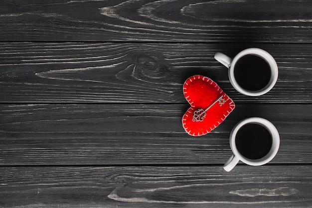 Cups of coffee near key on heart