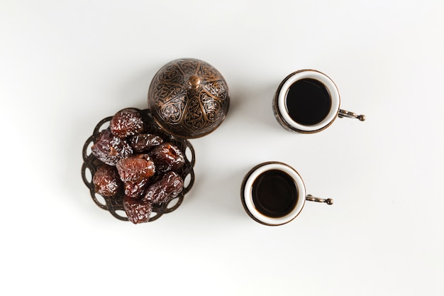 Cups of coffee near saucer with prunes