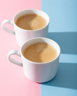 Cups of coffee on a pastel pink and blue background
