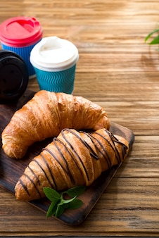 Cups of coffee and two croissants on the street in croissant cafe