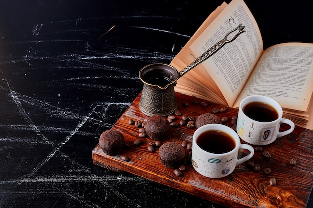 Cups of coffee with chocolate pralines.