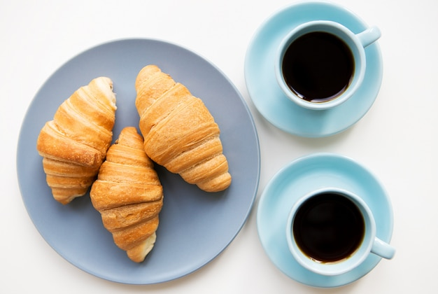 Cups of coffee with croissants