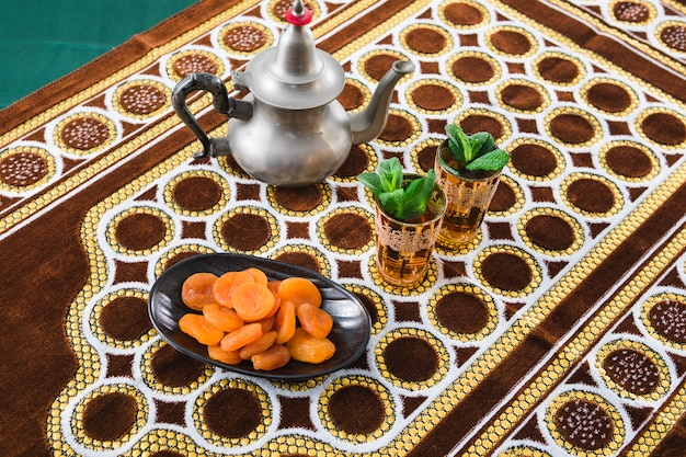 Cups of drink near teapot and dried apricots on mat