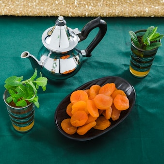 Cups of drink near teapot and dried apricots