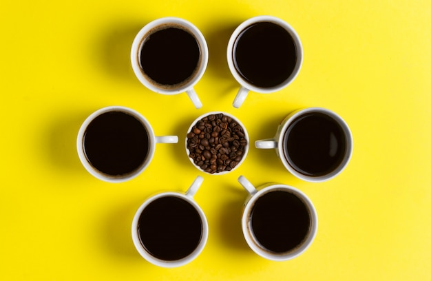 Cups of espresso coffee with coffee beans on yellow background