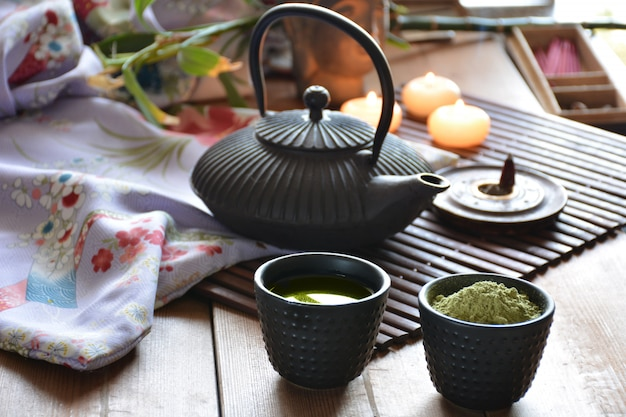 Cups filled with japanese tea kettle of hot water and incense and candles