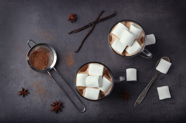 Cups of hot cocoa with marshmallows on grey table