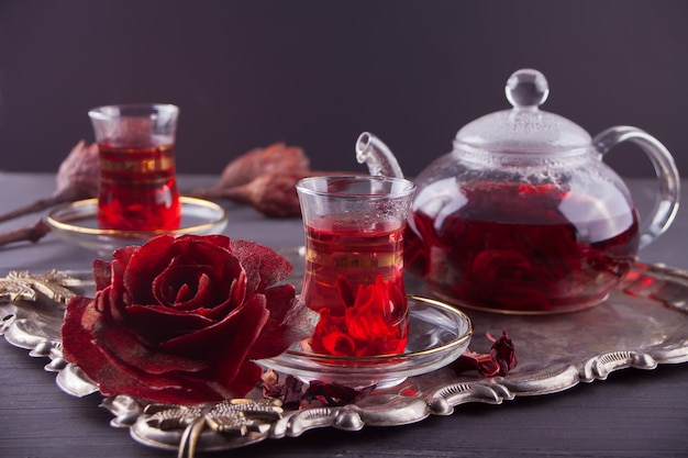 Cups of hot red karkade tea with teapot on the tray