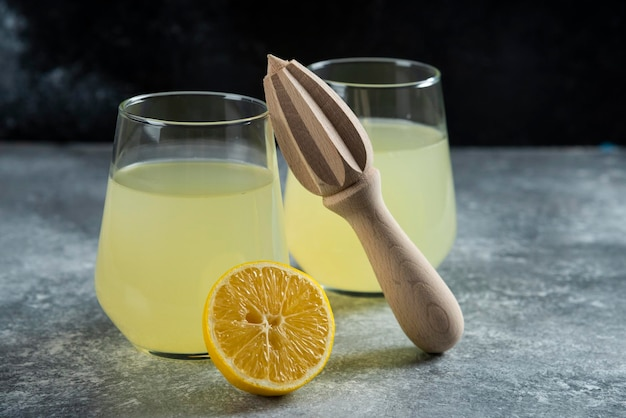 Cups of lemonade with slice of lemon and wooden reamer.