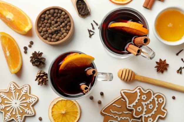 Cups of mulled wine and ingredients on white