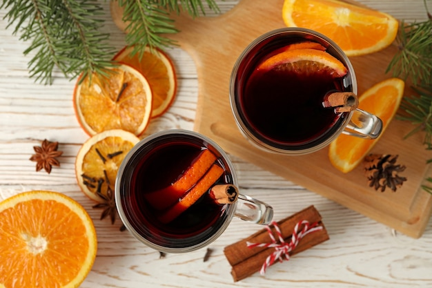 Cups of mulled wine and ingredients on wooden
