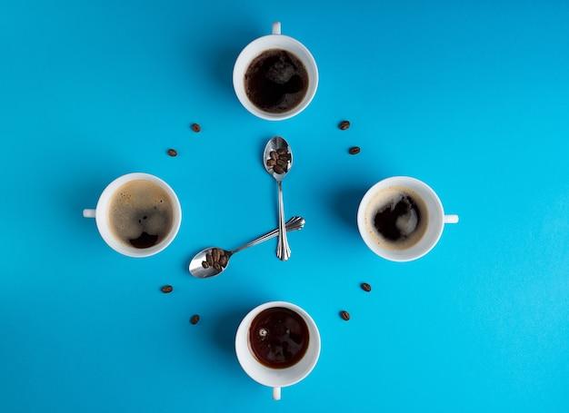 Чашки черного кофе и зерен, образующие циферблат с ложками на синем