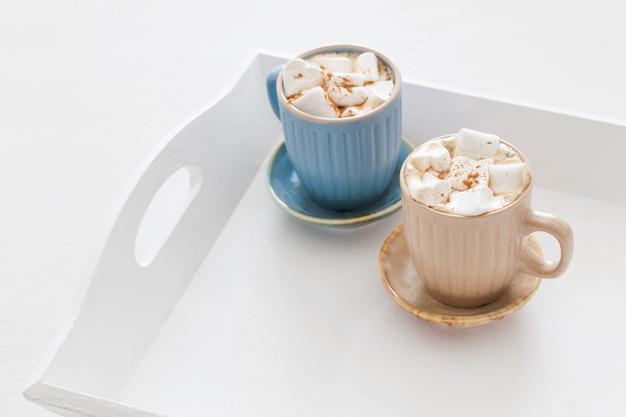 흰색 나무 쟁반에 마시멜로를 넣은 카카오 컵