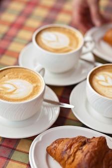 Чашки кофе капучино с круассаном в кафе