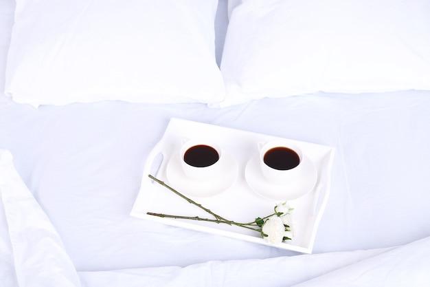 베개와 함께 편안하고 부드러운 침대에 커피 한잔