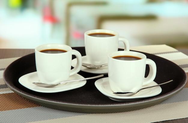 カフェのテーブルの上のトレイのコーヒー カップ