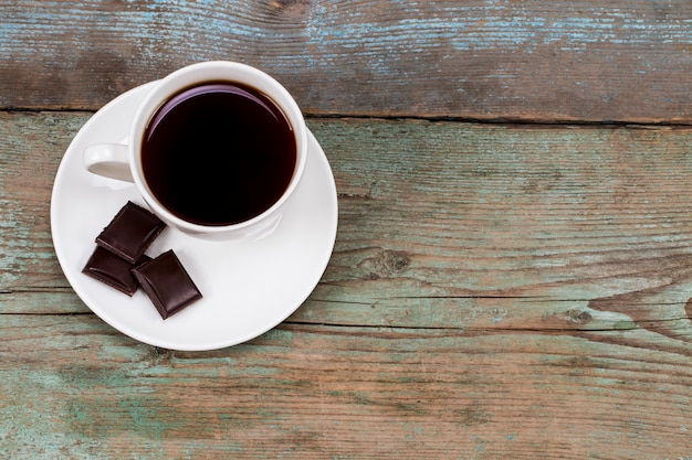 コピースペースのある木製のテーブルにチョコレートとコーヒーのカップ。