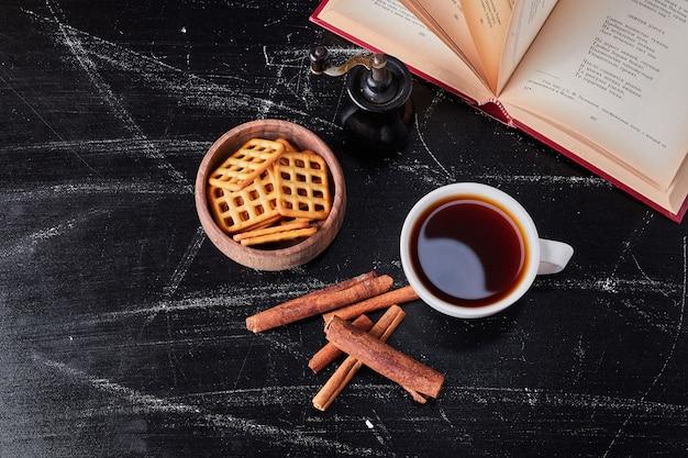 Чашки кофе с крекерами и корицей.