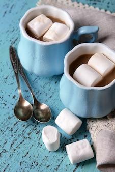 Чашки кофе с зефиром и салфеткой на деревянном столе
