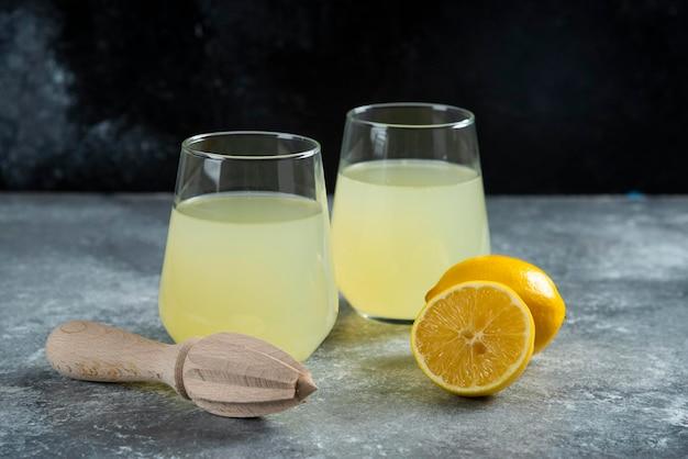 Чашки свежего лимонада с ломтиком лимона и деревянной разверткой.