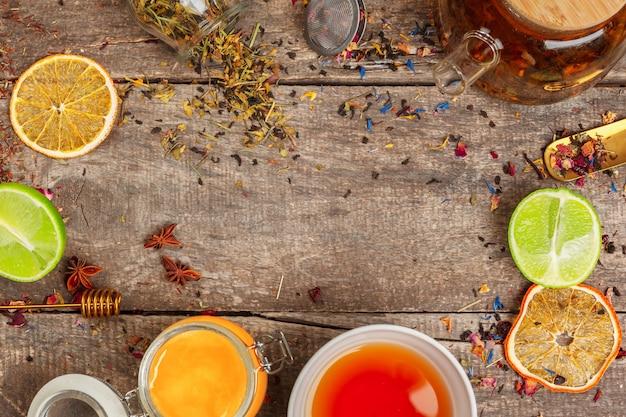 Чашки здорового травяного чая с корицей, сушеные розы и ромашки цветы в ложки на деревянном фоне, вид сверху